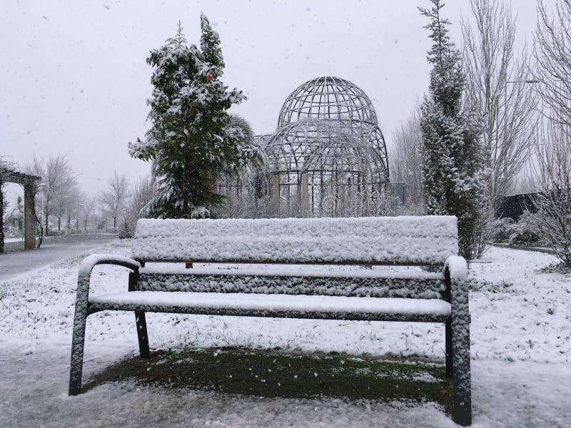 Eine schneebedeckte Bank im Winter lizenzfreies stockbild