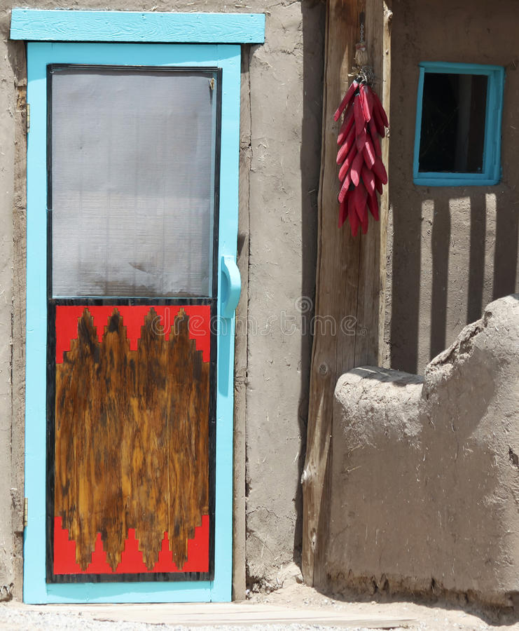Eine Schnur von Pfeffern Hung Outside eine Pueblo-Tür stockfoto