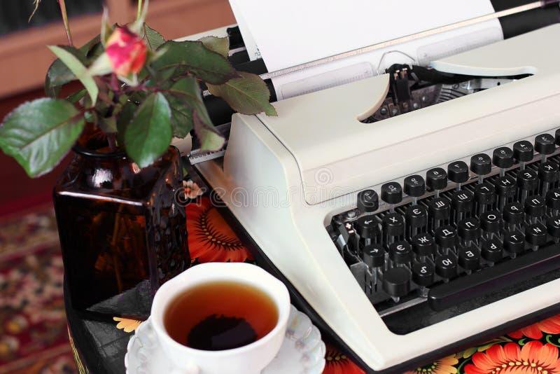Eine Schreibmaschine, Tee und eine Rose in einem Vase stockfotografie