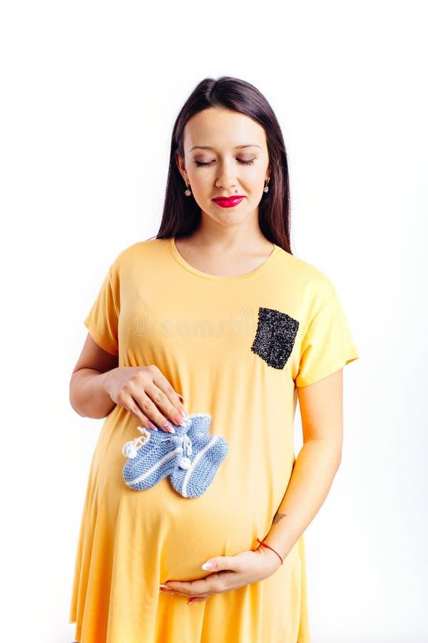 Eine schwangere Frau in einem Kleid und kleine Babysocken des Babys in ihren Händen lizenzfreies stockfoto