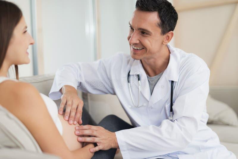 Eine schwangere Frau liegt auf einem hellen Sofa zu Hause Ein Doktor kam zu ihr, er prüft leicht ihren Bauch lizenzfreies stockfoto