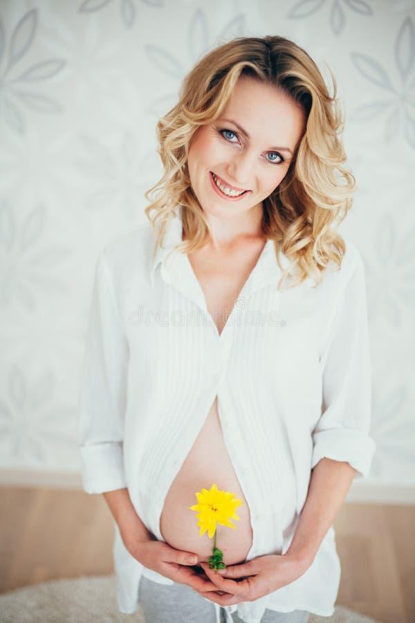 eine schwangere Frau mit Blume lizenzfreie stockfotografie