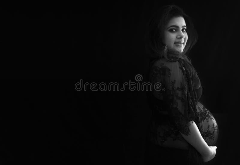 Eine schwangere indische Frau, die an der Kamera und an der Stellung gegen einen schwarzen Hintergrund lächelt lizenzfreie stockbilder