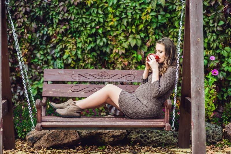 Eine schwangere junge Frau, die auf einem Schwingen, mit einer Tasse Tee sitzt Schwangere Frau, die im Park sich entspannt lizenzfreies stockbild