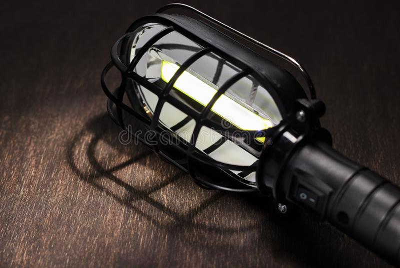 Eine schwarze tragbare Lampe glüht auf einen Holztisch stockfoto