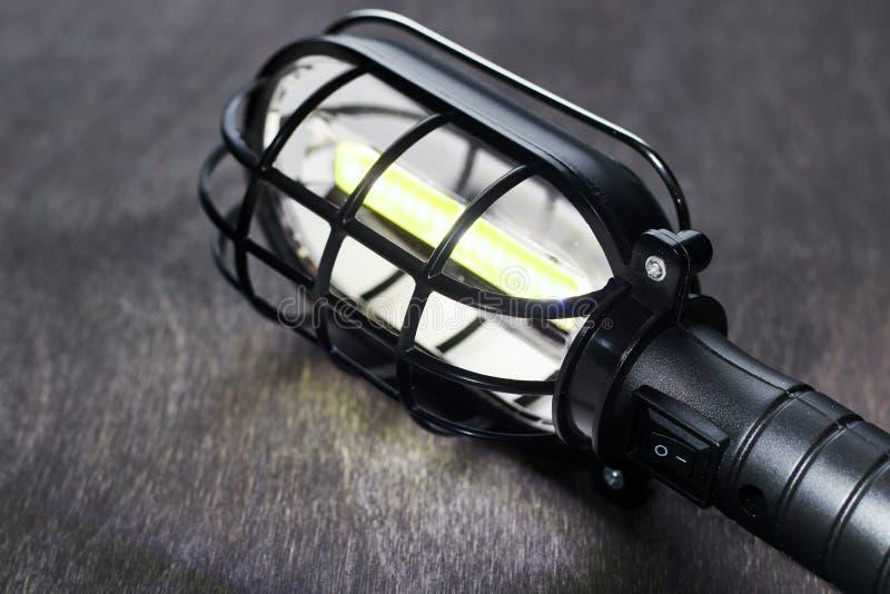 Eine schwarze tragbare Lampe glüht auf einen Holztisch lizenzfreie stockfotos