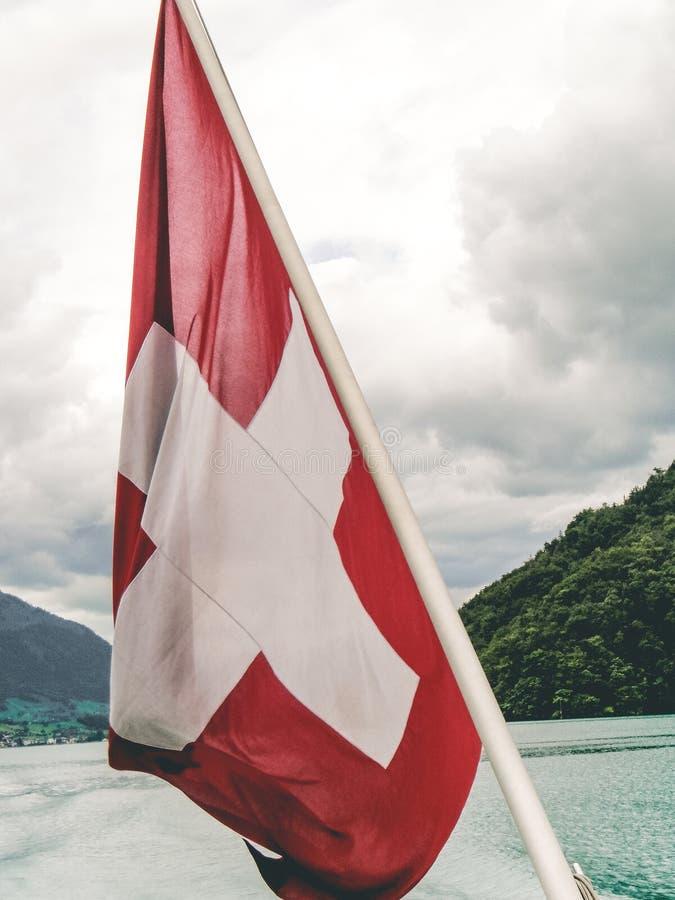 Eine Schweizer Flagge auf der Rückseite einer Fähre auf Luzerner See lizenzfreie stockfotos