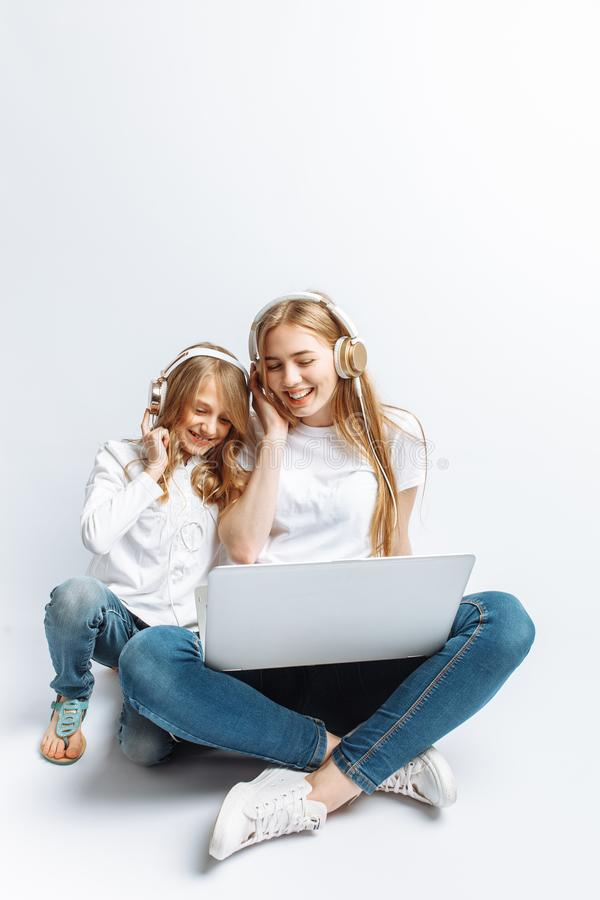 Eine Schwester oder eine junge Mutter mit ihrer Tochter, die einen Film auf meinem Laptop, Spaß, lachend, Studio aufpasst, lokali stockfotos