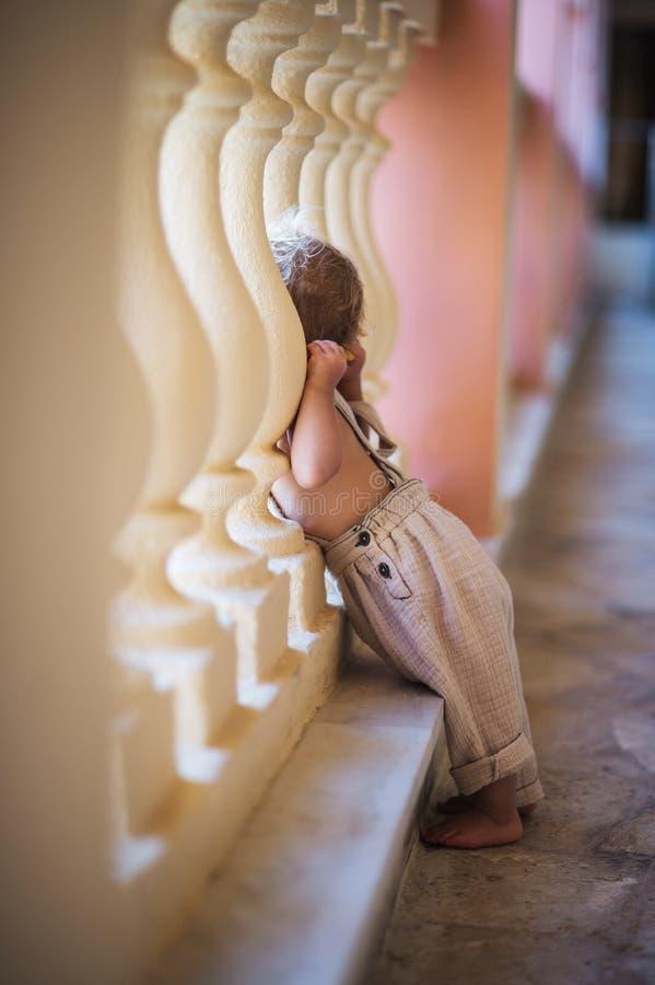 Eine Seitenansicht des kleinen Kleinkindmädchens, das durch konkretes Geländer an den Sommerferien schaut lizenzfreie stockfotografie