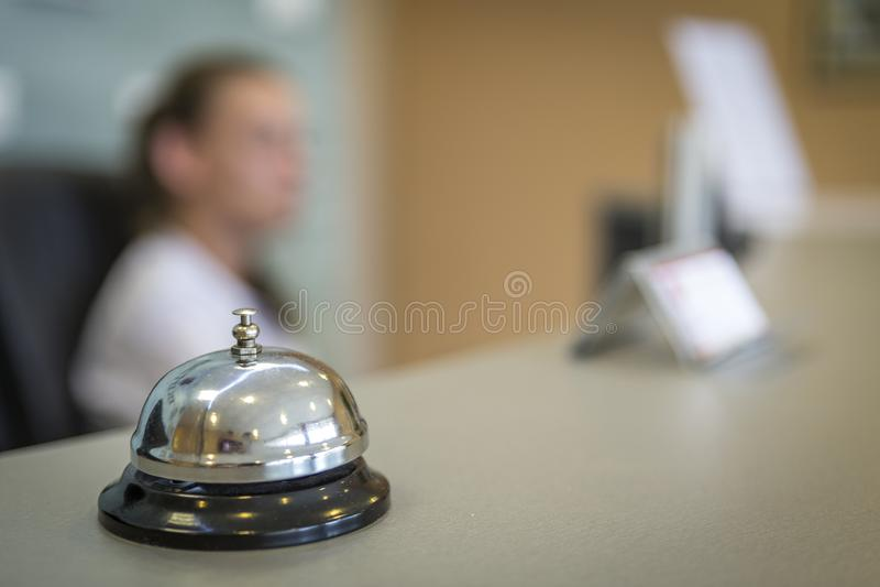 Eine silberne Glocke eines Hotels, zum von Gästen gegen eine undeutliche Empfangsdame zu treffen stockfotografie