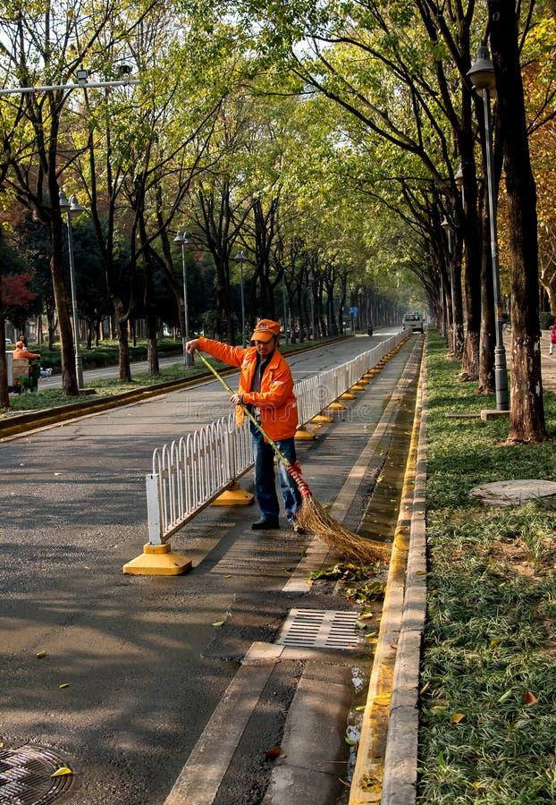 Eine snitation Arbeitskraft, welche die Straße fegt stockfotos