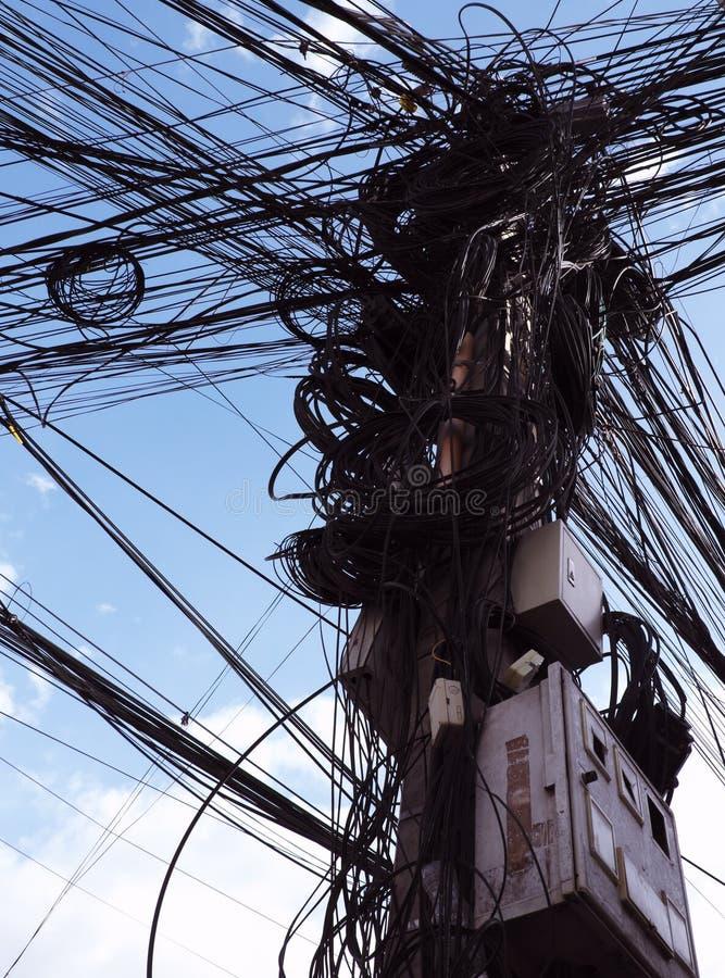 Eine Spalte von Stromleitungen mit einer gro?en Anzahl verwirrten Dr?hten Zeile des Stroms Chaos und der Einsturz des st?dtischen stockfotos