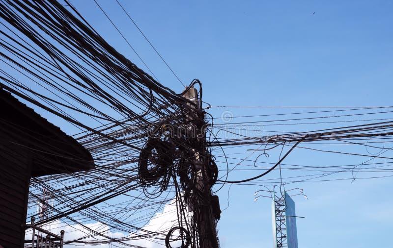 Eine Spalte von Stromleitungen mit einer gro?en Anzahl verwirrten Dr?hten Zeile des Stroms Chaos und der Einsturz des st?dtischen stockfoto