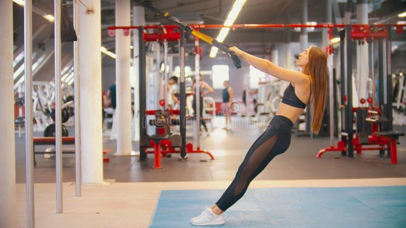 Eine sportive Frau in der Sportkleidung ausbildend in der Turnhalle - die Griffe halten und lehnt sich zurück stockbild