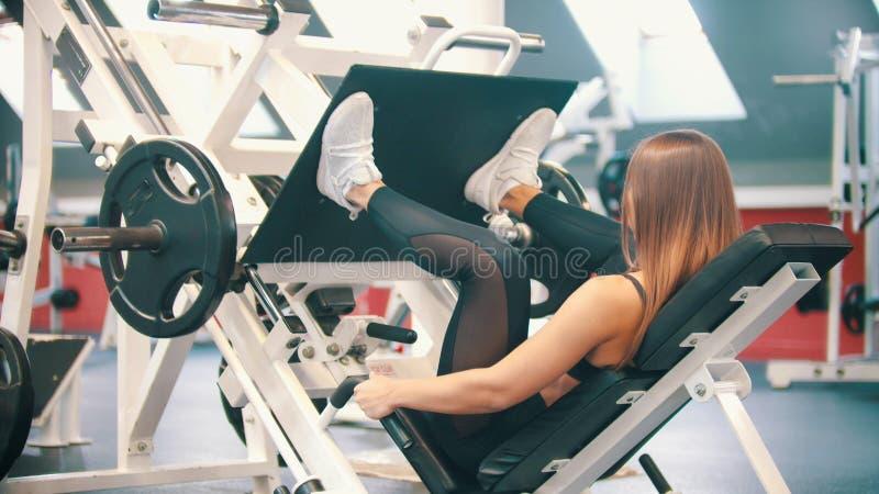 Eine sportive Frau in der Turnhalle - Ausführung einer Beinpresse, die auf dem Ausbildungsapparat trainiert lizenzfreie stockfotos
