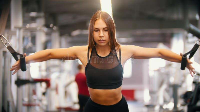 Eine sportive Frau mit langem Haartraining in der Turnhalle - die Griffe ziehend - Ausbildungshände stockbilder