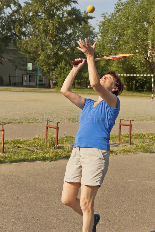 Eine Sportlerin der älteren Personen spielt Tennis stockbilder