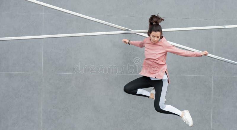 Eine sportliche junge Frau springt, macht Akrobatik, Ballett, ist aktiv am Sport beteiligt, gegen eine Betonwand Wand aus Beton. stockfoto