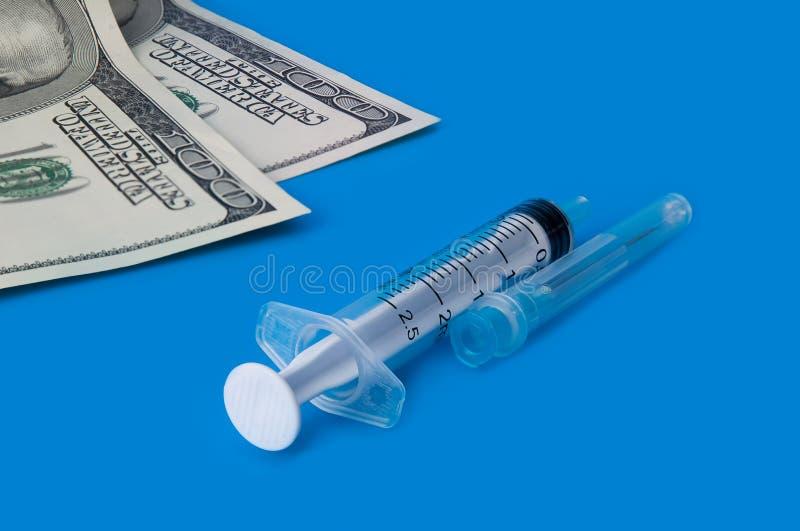Eine Spritze und hundert Dollarscheine auf einem blauen Hintergrund lizenzfreies stockfoto
