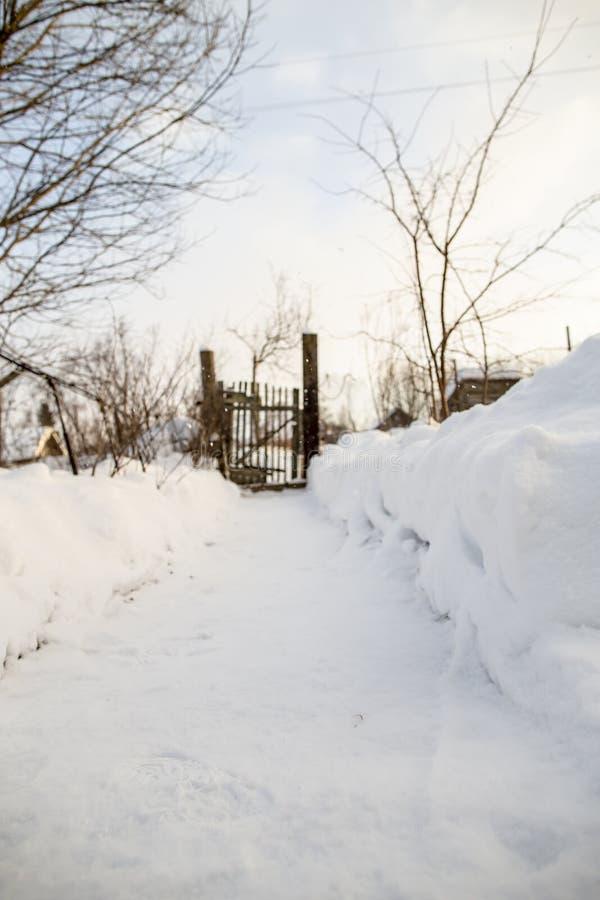 Eine Spur, die vom Schnee geklärt wird, führt zu ein altes, gebrechliches Tor und ein fenc stockfoto