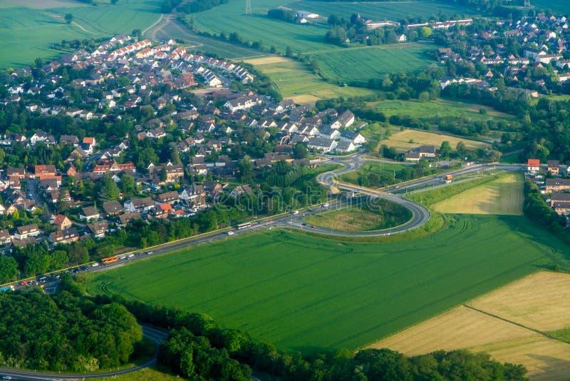 Eine Stadt mit den niedrigen Häusern umgeben durch Landstraße die Ansicht von der Spitze der Troposphäre stockfotos