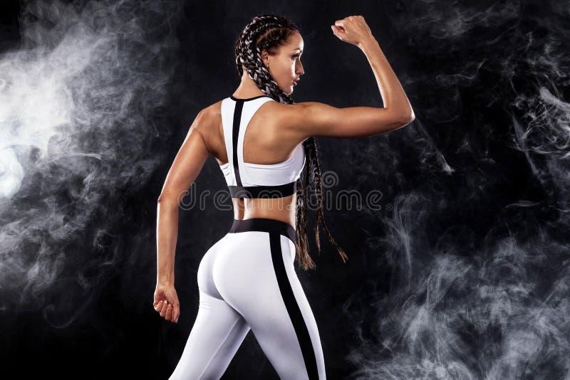 Eine starke athletische Frau auf dem schwarzen Hintergrund, der in der weißen Sportkleidungs-, Eignungs- und Sportmotivation träg stockbild