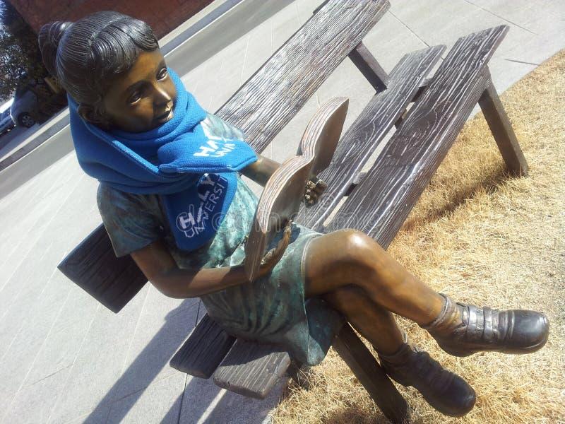 Eine Statue eines Mädchens, das ein Buch beim Sitzen auf der Holzbank mit Schalldämpfer um Hals liest stockfoto
