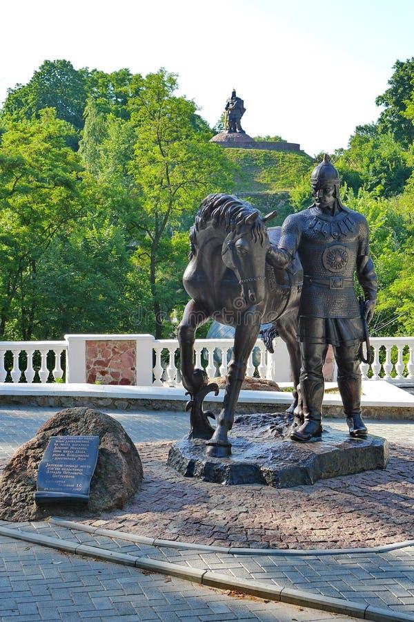 Eine Statue eines Ritters in einem Sturzhelm, der ein Pferd vor dem hintergrund der grünen Bäume auf einer Steigung und einem Mon lizenzfreie stockfotografie