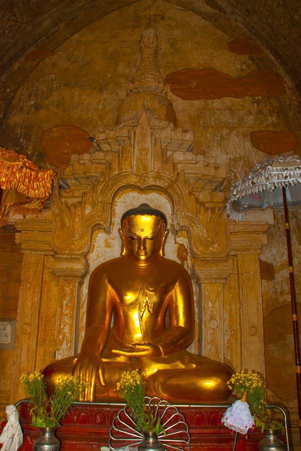 Eine Statue von einem goldenen Sitz-Buddha im Tempel in Bagan, Myanmar birma stockfotos
