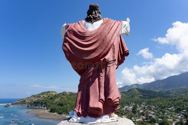 Eine Statue von Jesus Christ legte auf einen Hügel und stellte den Ozean und ein Dorf in Flores, Ost-Nusa Tenggara, Indonesien ge stockfotos