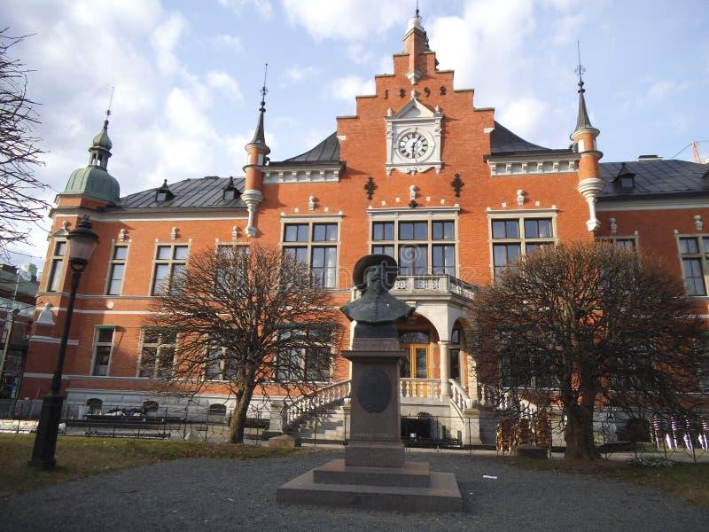 Eine Statue vor einem historischen roten Haus in Umea stockbilder