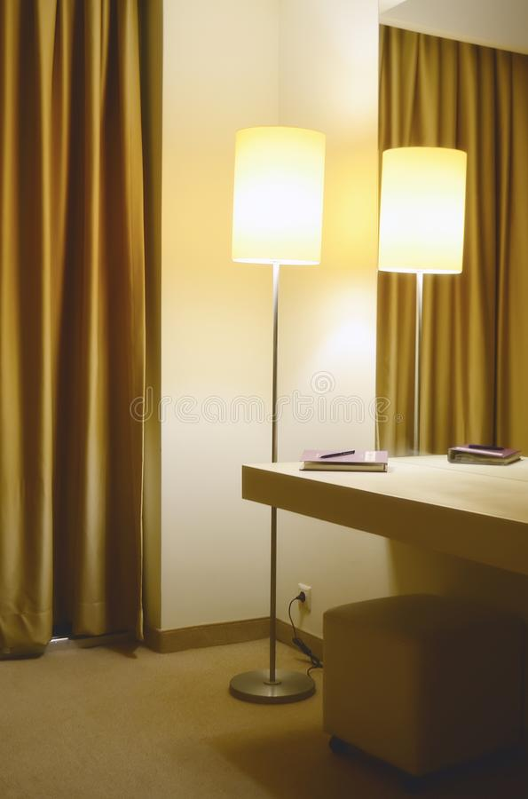 Eine Stehlampe in der Ecke des Hotelzimmers Ein Spiegel und eine Konsole mit einem Notizbuch und ein Stift auf ihm stockbilder