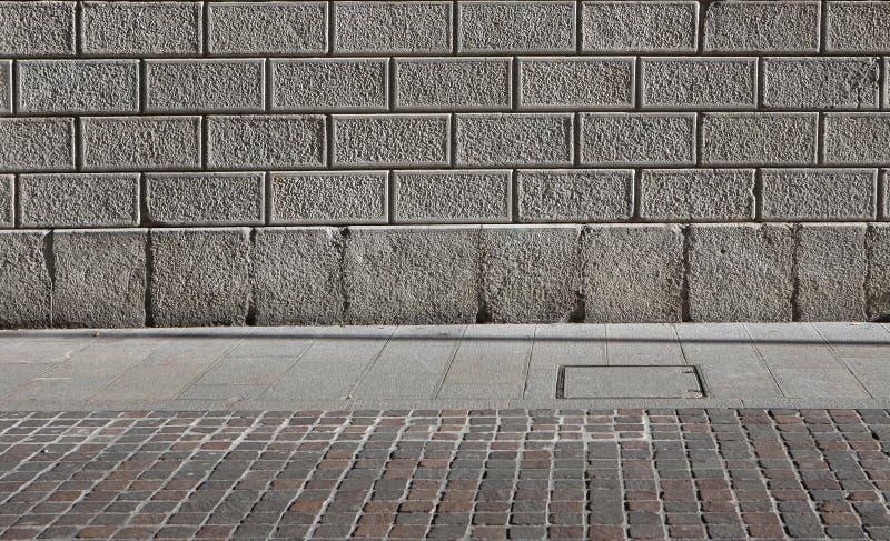 Eine Steinblockfassade, ein grauer Natursteinplattenbürgersteig und ein porphyr stockbild