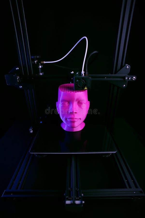 Eine Stellung 3D-FDM-printer im dunklen Neonumgeben stellt einen humanoid Kopf vom rosa Plastik her stockbild