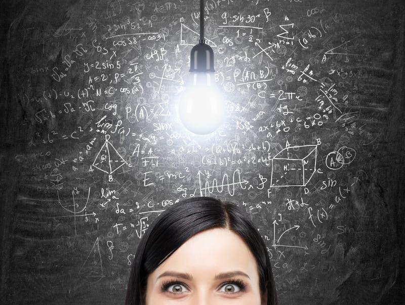 Eine Stirn der Brunettefrau, die an Lösung des schwierigen mathematischen Problems denkt Matheformeln sind auf der schwarzen Tafe lizenzfreies stockbild