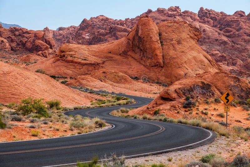 Eine Straße läuft durch sie im Tal des Feuer-Nationalparks, Nevada, USA stockfotos