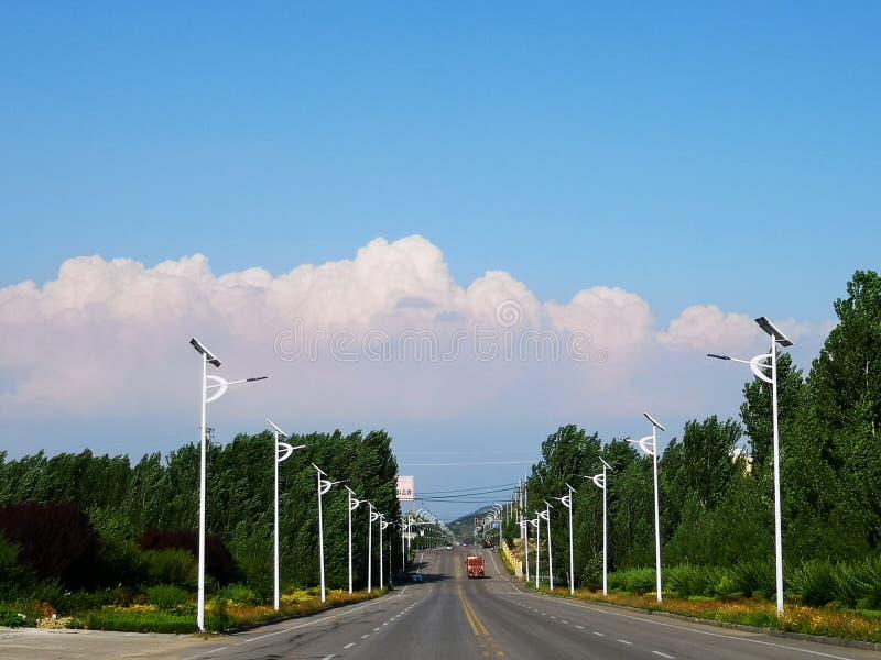 Eine Straße mit vielen Beitrag unter den weißen Wolken stockbild