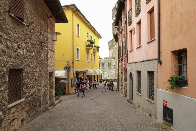 Eine Straße nahe mittelalterlichem Schloss mit touristischen Geschäften und Café in Sirmione, Italien lizenzfreies stockbild