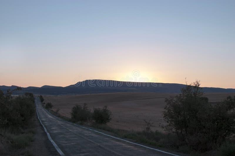 Eine Straße zwischen einigen goldenen Wiesen auf Sonnenaufgang lizenzfreies stockbild