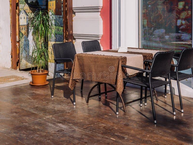 Eine Tabelle mit Stühlen eines Stuhls nahe dem Fenster eines Sommercafés stockbild