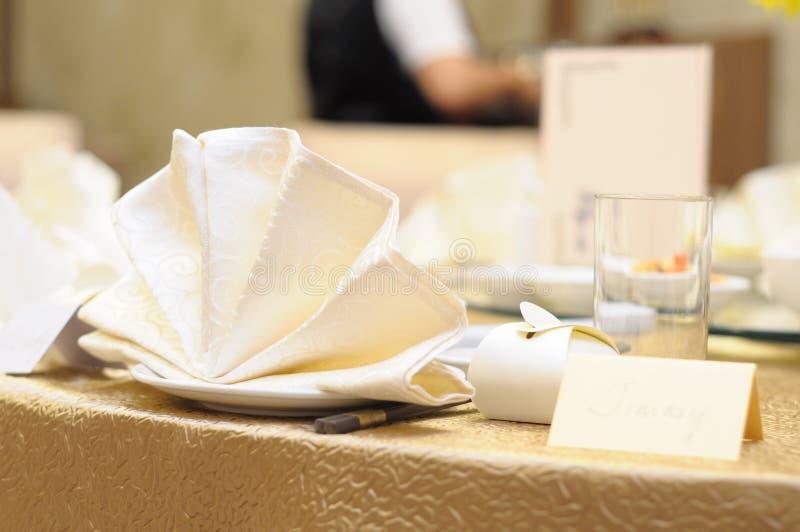 Eine Tabelleneinrichtung des beige und milchigen weißen Geschirrs, der Servietten und der Gastnamenkarte an einem asiatischen Res stockfotografie