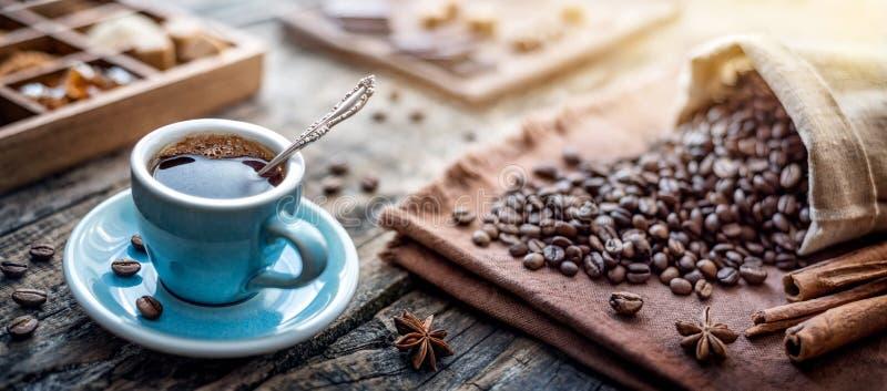 Eine Tasse aromatischen schwarzen Kaffee und Kaffeebohnen auf dem Tisch Morgens Kaffee Espresso zum Frühstück in einer schönen bl stockfoto