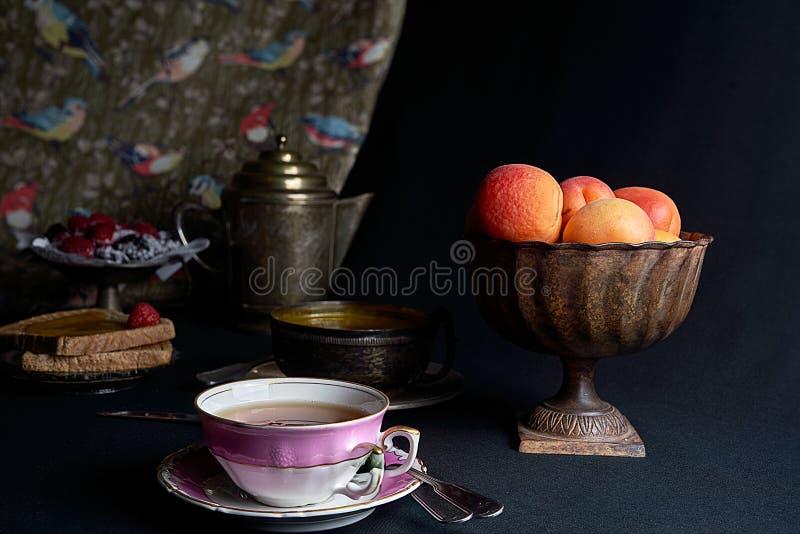 Eine Tasse Tee begleitete von den frischen Aprikosen, von der Aprikosenmarmelade und von einem Behälter von Beeren stockfotografie