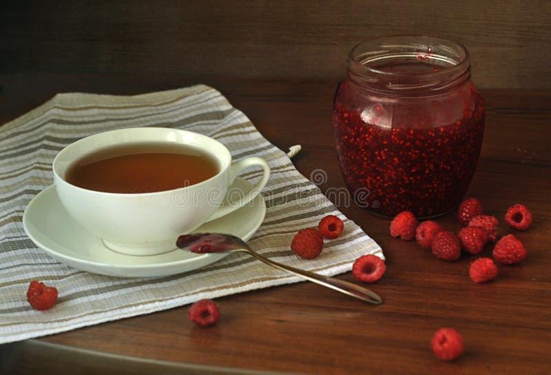 Eine Tasse Tee, ein Glas selbst gemachte Himbeermarmelade und Himbeerbeeren auf einem Holztisch lizenzfreie stockfotos
