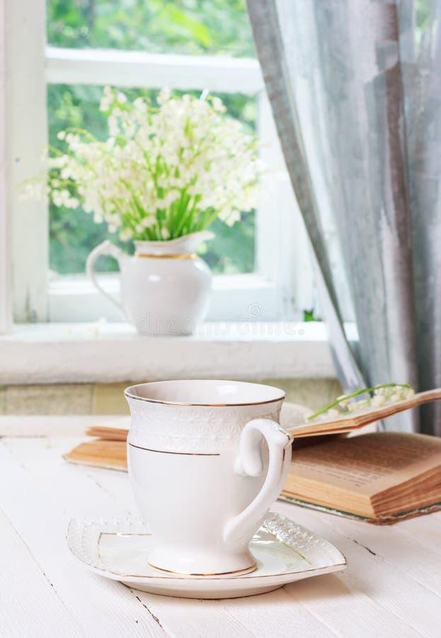 Eine Tasse Tee oder Kaffee und ein Buch auf einer weißen hölzernen antiken Retro- Tabelle und ein Blumenstrauß von Maiglöckchenbl stockfotos