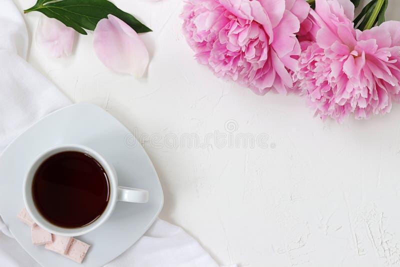 eine Tasse Tee, eine Tischdecke, Blumenpfingstrosen, Blumenblätter und Blatt auf einer weißen Tabelle lizenzfreies stockbild