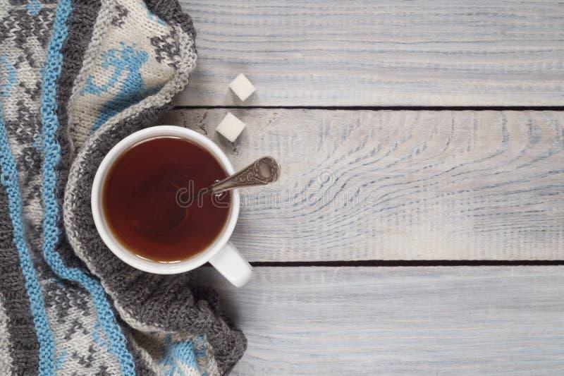 Eine Tasse Tee und ein gestrickter Schal auf dem Hintergrund eines weißen wo stockbild