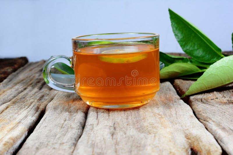 eine Tasse Tee und Grünzitrone verlässt auf altem Holztisch stockfotos