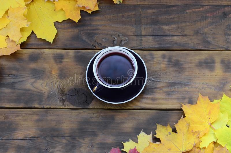Eine Tasse Tee unter einem Satz des Gelb färbens des gefallenen Herbstlaubs auf einer Hintergrundoberfläche von natürlichen hölze stockfoto