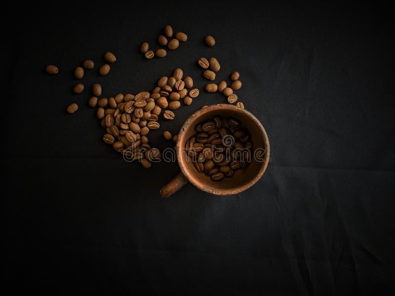 Eine Tonwarenschale und Kaffeebohnen auf schwarzem Hintergrundhintergrund stockfoto